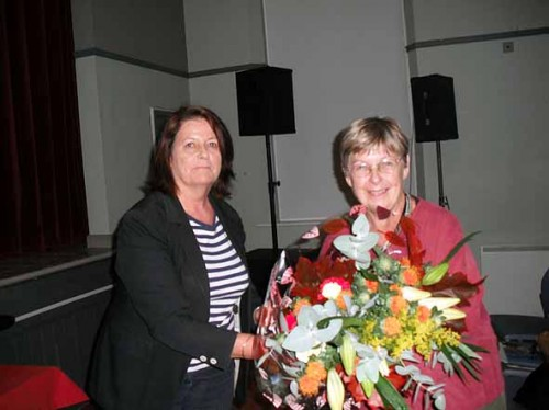 Dr. Dagmar O'Riain Raedel receiving a bouquet of flowers from committee member Mary O'Callaghan